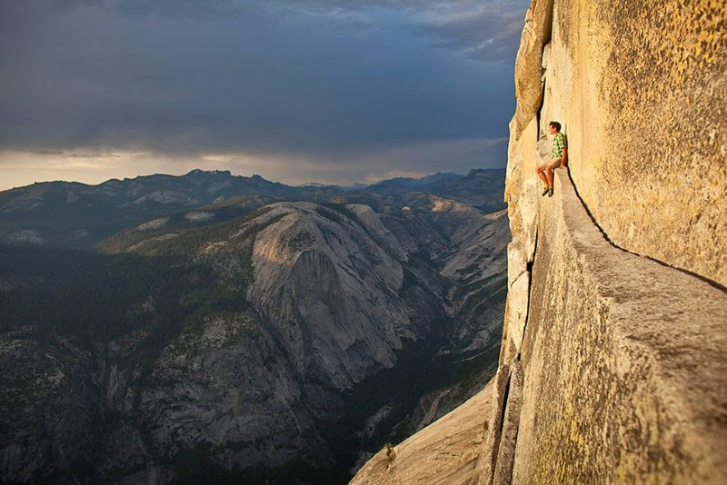 Alex Honnold, relaxing in the middle of the climb at Half Dome, Yosemite National Park, USA