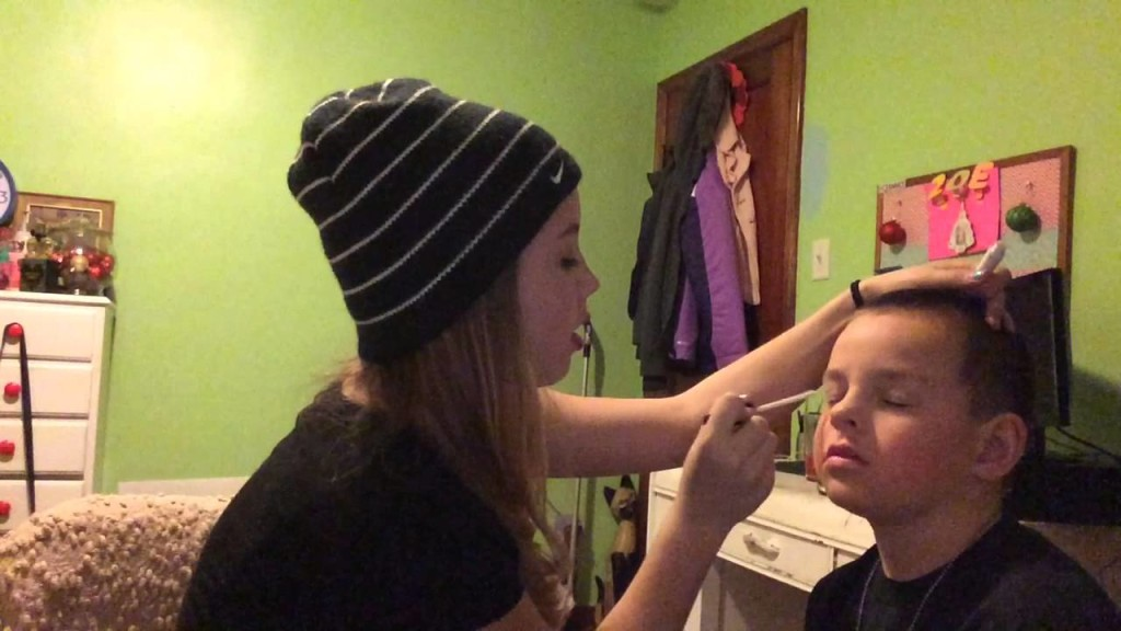 sister doing makeup on brother